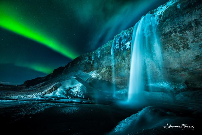Northern Lights shine over waterfall Seljalandsfoss