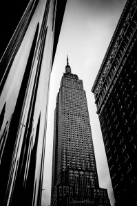 Travel Images Empire State Building seen betwen shiny and textured buildings